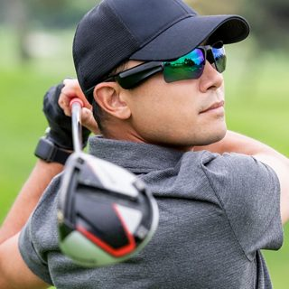 Man golfing wearing Bose Frames Tempo with Trail Blue lenses