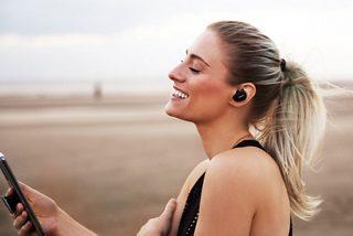 Woman looking at her smartphone wearing Triple Black Bose Sport Headphones on a beach