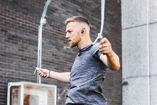 Man jumping with a skipping rope wearing Triple Black Bose Sport Earbuds