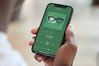 Мъж, държащ мобилен телефон, възпроизвеждащ музика