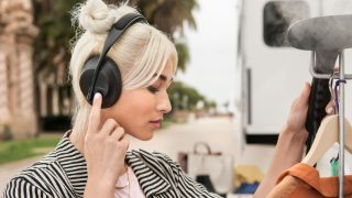 Woman wearing Bose Noise Cancelling Headphones 700 using the touch controls