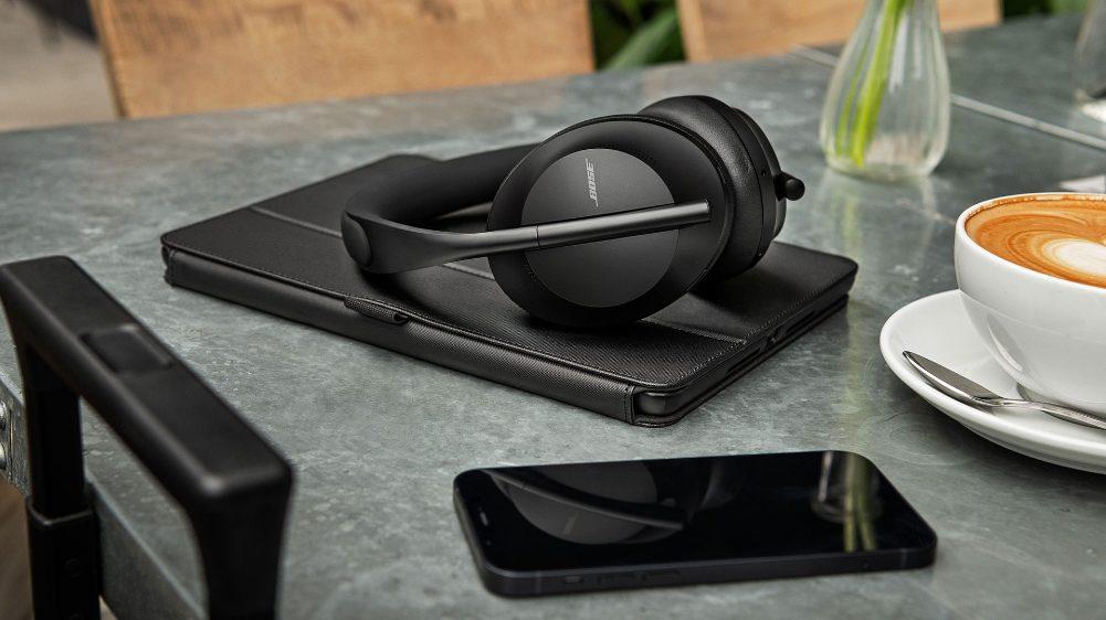 Casque Bose Noise Cancelling Headphones700 sur une table, avec une tablette et un smartphone