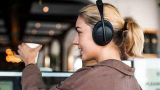 Una mujer usando los audífonos con cancelación de ruido Bose Headphones 700 en público