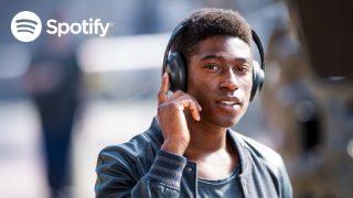 Logotipo de Spotify y hombre tocando y sosteniendo el casco derecho para escuchar música por Spotify