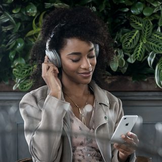 Woman wearing QuietComfort 35 headphones using the Action button