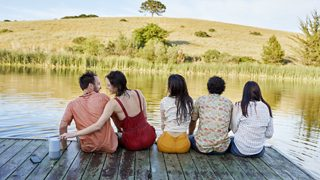 Friends sitting on a dock listening to a Bose Portable Smart Speaker