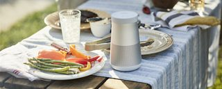 SoundLink Revolve+ II Bluetooth speaker on a table at an outdoor barbecue