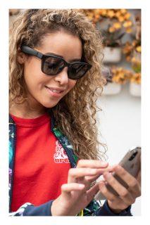 Woman using her phone wearing Bose Frames Alto